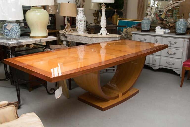 This highly polished Italian handmade table is in rectangular form. The top is supported by a base with arches and is joined by a conforming rectangular base. The top is banded and has a geometric diamond inlaid form flanked by triangles. The table