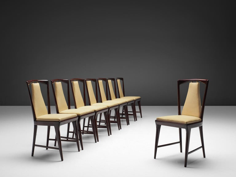 Set of eight dining chairs with beige faux leather and mahogany frame, Italy, 1950s.   These classic chairs have square seats and delicately shaped backs. The beige seat and back element is connected to the stained mahogany frame via brass joints