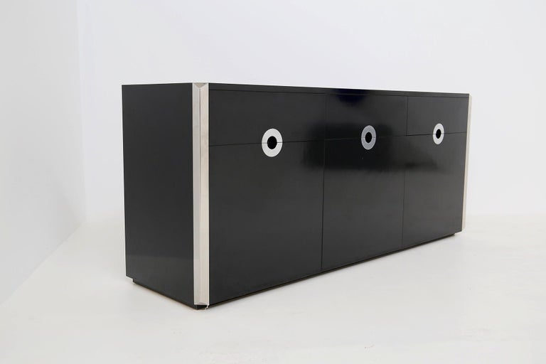 Elegant and sturdy sideboard designed by Willy Rizzo in 1970s.  The sideboard was made for Mario Sabot. The sideboard has a sturdy structure in black lacquered wood. The peculiarity of the sideboard is its triangular steel profiles. Another