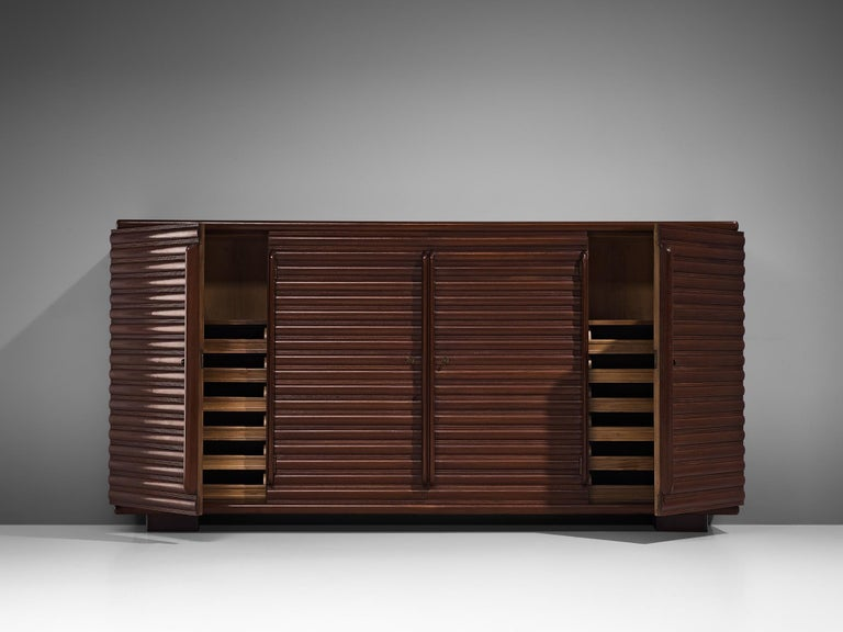 Sideboard, oak, Italy, 1950s.  Beautiful and elegant Italian sideboard with carved surface. It shows a pattern stained wooden structure, build up from repeating horizontal lines. The side board is high and rests on two sturdy feet. The design is
