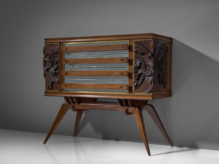 Italian elegant sideboard in oak originates from the 1940s. The two outer door panels show a very detailled relief of floral motifs, which give this sideboard an expressive touch. Behind the carvings storage facility can be found on each side.