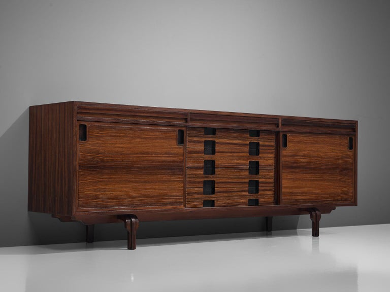 Luigi Massoni, sideboard, rosewood, Italy, 1960s  This Italian credenza designed by Luigi Massoni is executed in rosewood. It consists of two sliding doors with characteristic black handles and four drawers. The cut-out handles are rectangular