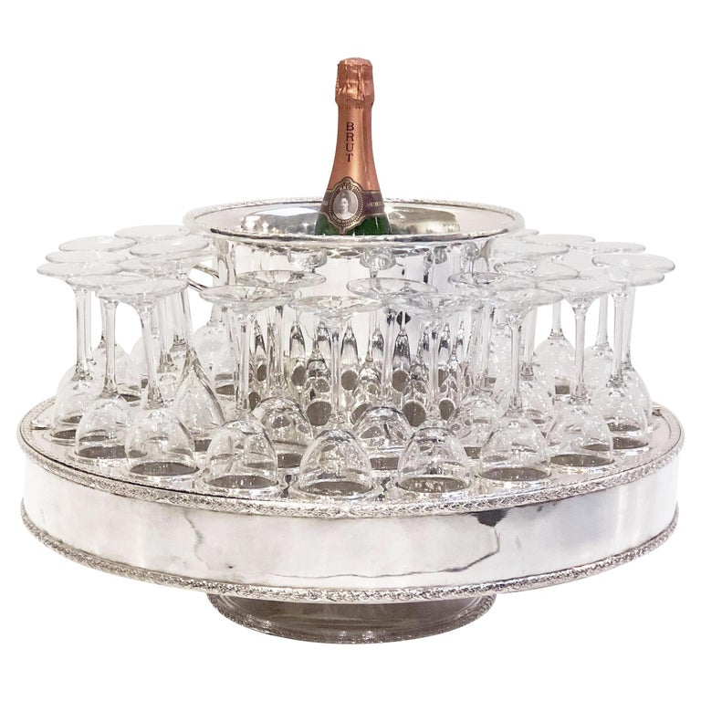 A fine Italian champagne service or presentation centerpiece, featuring a round revolving stand (or lazy susan) of plate silver, with fitted spaces for holding thirty-two champagne flutes and a removable champagne or wine cooler in the inset