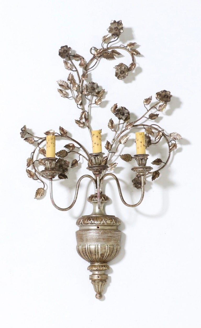 Gorgeous, Italian 1950s silvered iron and wood pair of sconces.  Each sconce consists of an urn-shaped silver-leafed wood base with a spray of iron branches and carved wood flowers.   The sconces are wired and in working condition, they require