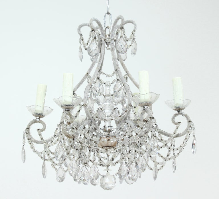 Exquisite, Italian 1940s silvered iron and crystal beaded chandelier. This rare beauty is composed of a scrolled iron frame which was meticulously wrapped with tiny silvered glass beads through its entirety. An abundance of macaroni glass bead