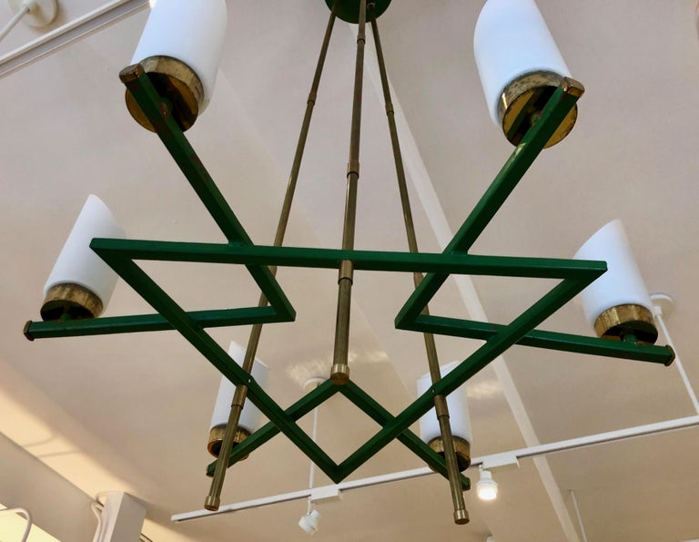 Chic, architectural design in brass, glass and enameled metal. Six upright lights sit on a green metal grid that is suspended by three brass rods.