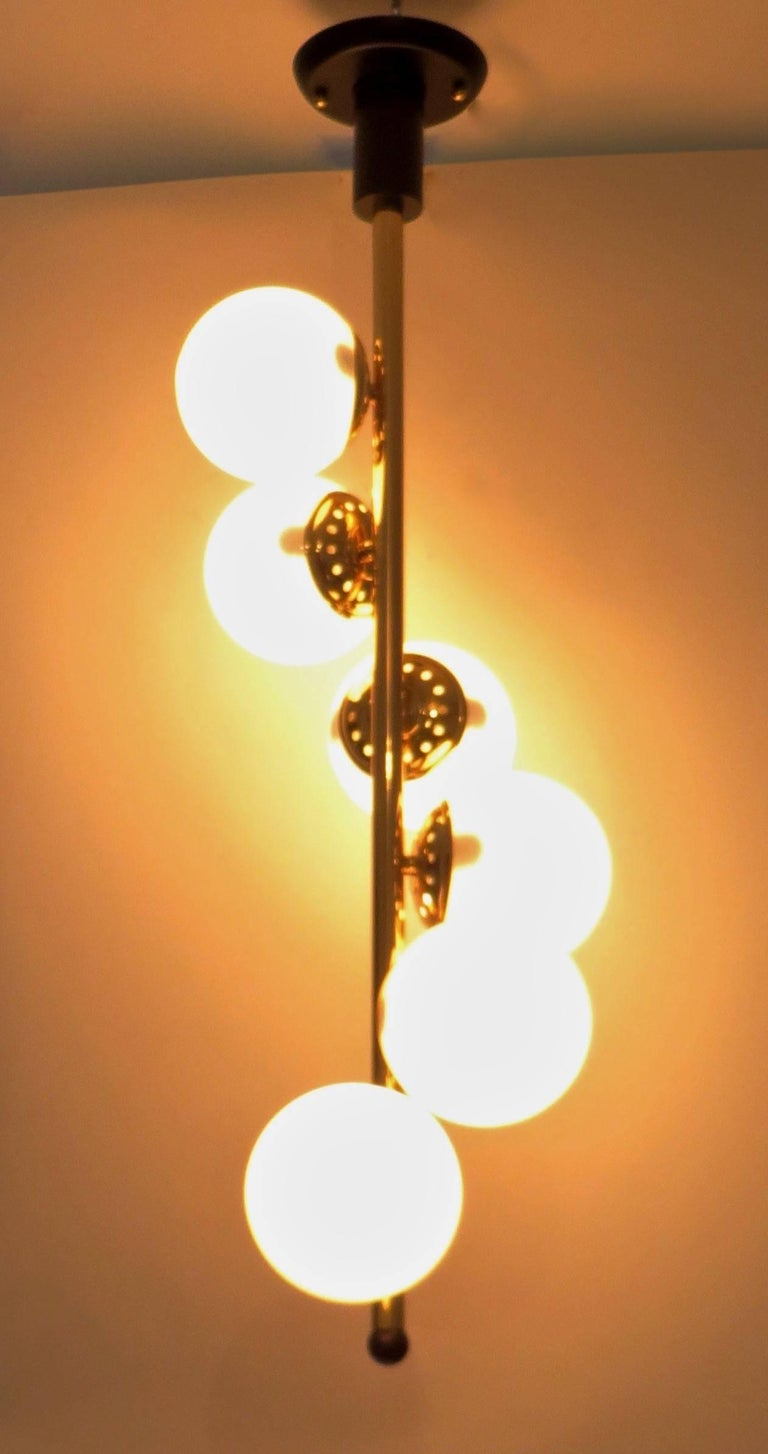 Mid-Century Modern Italian Six-Light Brass and Glass Chandelier with Opaque White Globes, Stilnovo For Sale