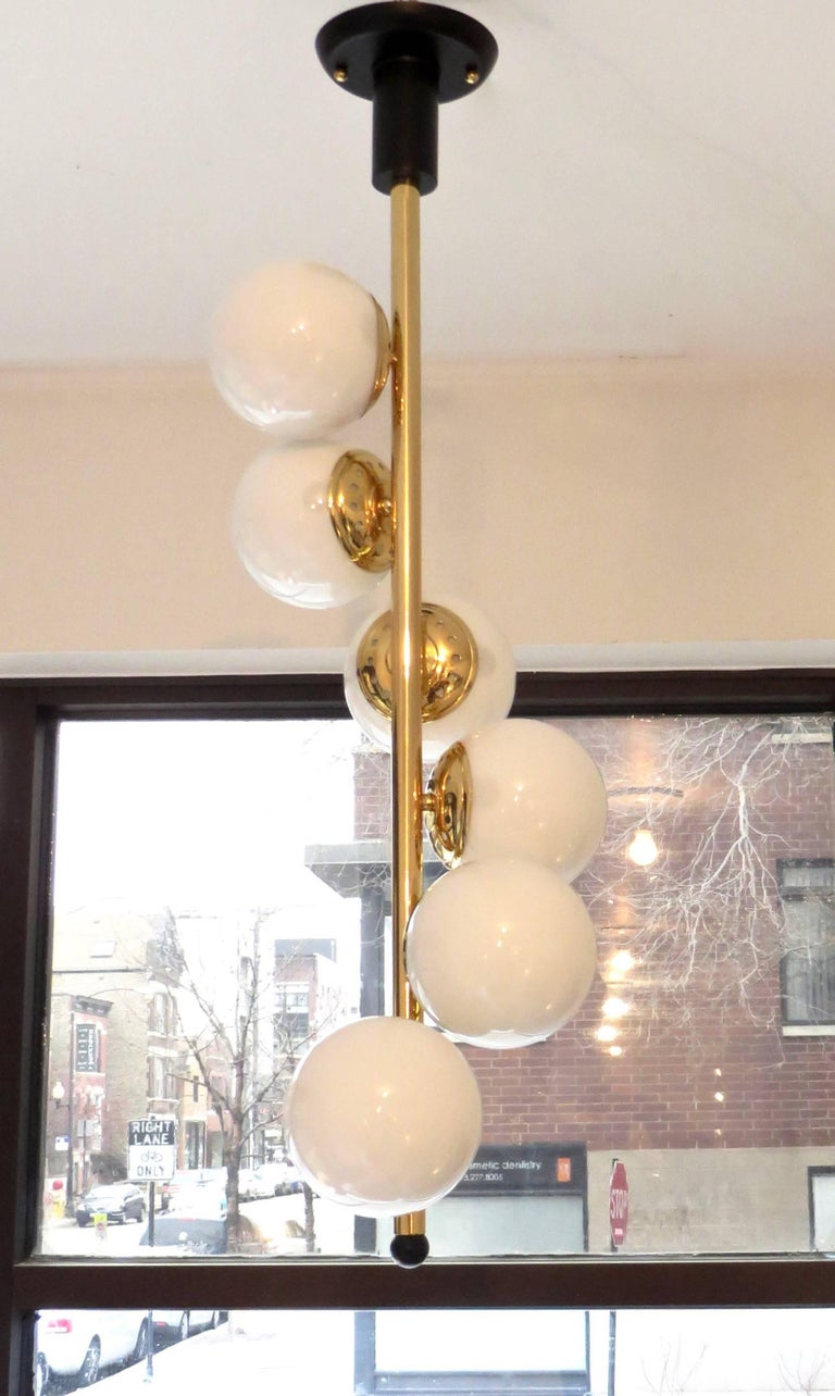 Mid-20th Century Italian Six-Light Brass and Glass Chandelier with Opaque White Globes, Stilnovo For Sale