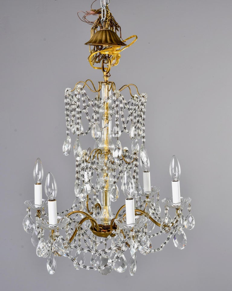 Italian chandelier has six candle style lights with candelabrum sized sockets, faceted tear drop shaped crystals and beaded swag, circa 1930s. Unknown maker. Rewired for US electrical standards.