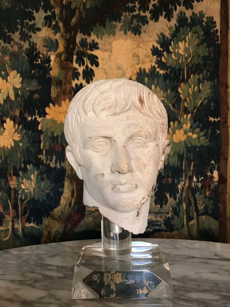 Very decorative bust of Augustus Caesar. Bust is cast stone (concrete), not carved stone and raised on an acrylic base. After the Antique, 20th century rendition. Having rough hewn neck. With pitting/air pockets throughout. Seam from top to back of