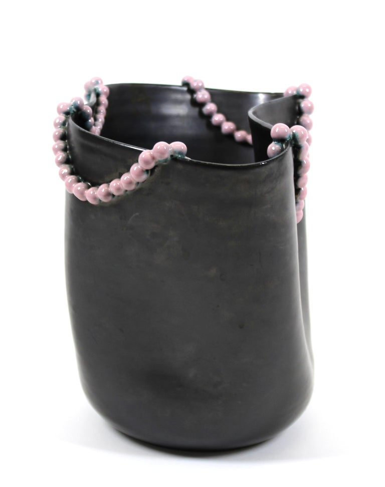 Italian Surrealist glazed ceramic undulating vase in gun metal black, with an applied string of delicate pink ceramic pearls. Handmade in Italy during the 1940s, the piece has a partly illegible makers mark on the bottom. In great vintage condition