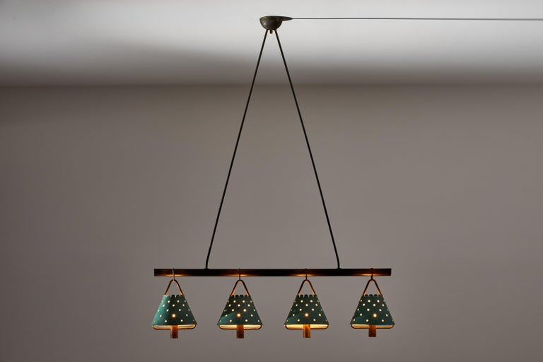 Four shade Italian suspension light designed and manufactured in Italy, circa 1940s. Perforated shades made of original enameled aluminum, walnut stretcher, brass hardware. Original brass canopy. Rewired for U.S. junction boxes. Takes four E27