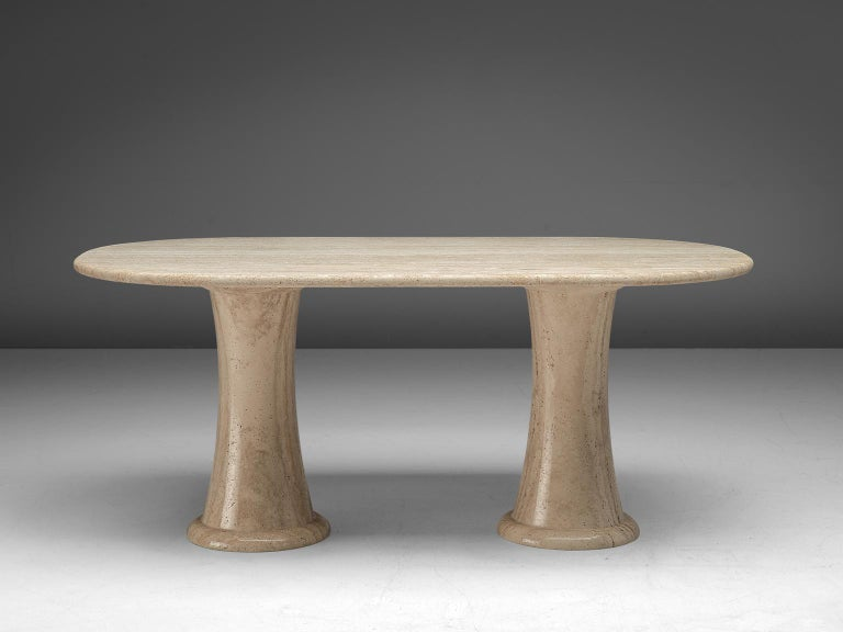 Dining table, travertine, Italy, 1970s.  This sculptural center table is a typical example of postmodern design. The dining table is executed in travertine by means of which a warm, natural yet monumental look is created. The thick, oval top rests