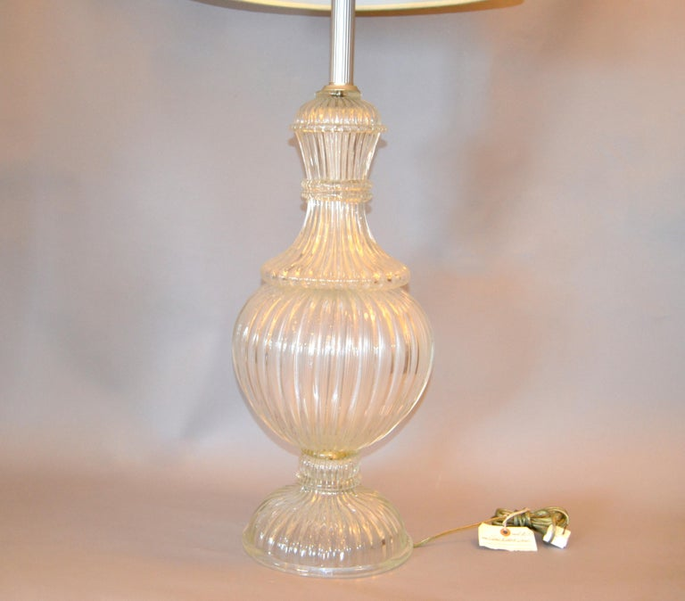 Italian tall clear hand blown feminine-shaped ribbed Murano glass table lamp. The top has an aluminum ribbed neck. In perfect working condition and uses a max. 60 watts light bulb. No shade.