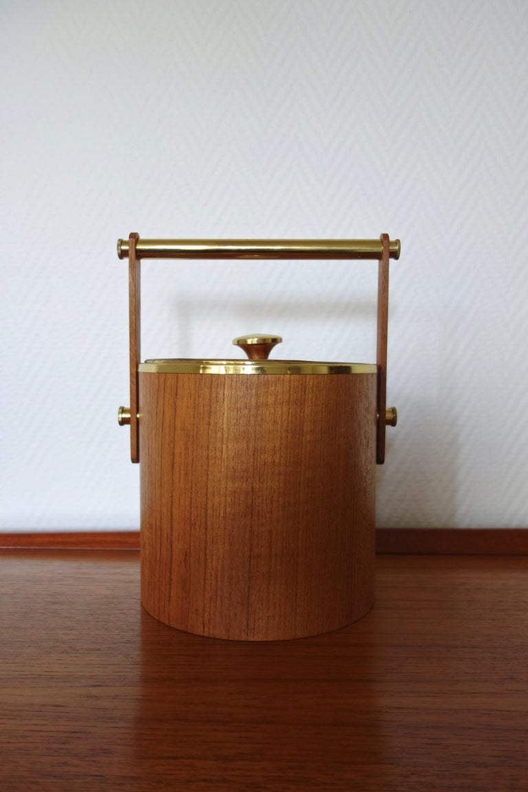 Italian ice bucket from the 1960s. Stamped with iron underneath. Clean and timeless line, this article is made of solid teak and aged brass. Complete and original, its handle is flexible, and it is completely removable (perfect for maintenance).
