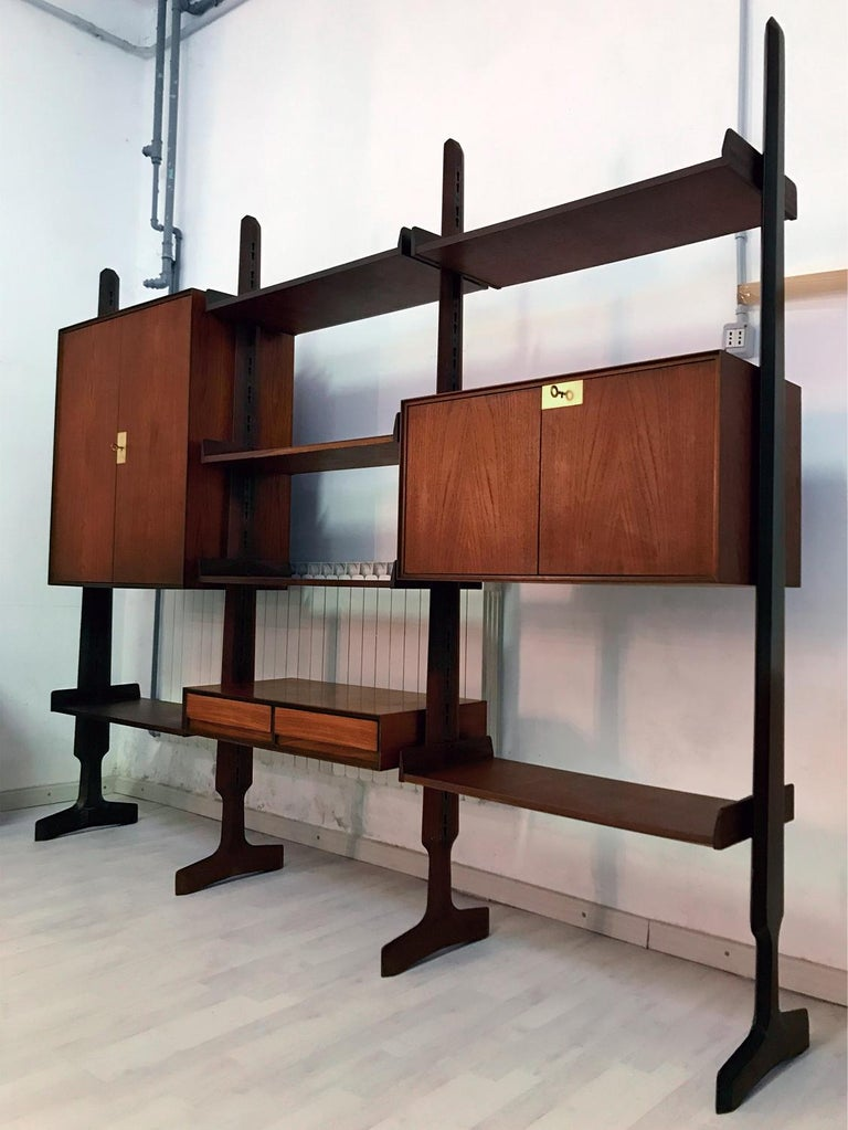 This bookcase is composed by three modules freestanding, suitable to be moving and placed at will in the home, equipped with six shelves, two cabinets with doors, and one cabinet with two drawers. It's a versatile item that offers plenty of room for