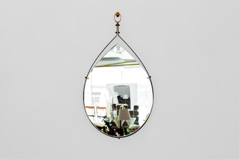 1950s Italian iron and brass tear dropped shaped mirror with perforated brass detail within the edge.  Brass hardware and new mirror.
