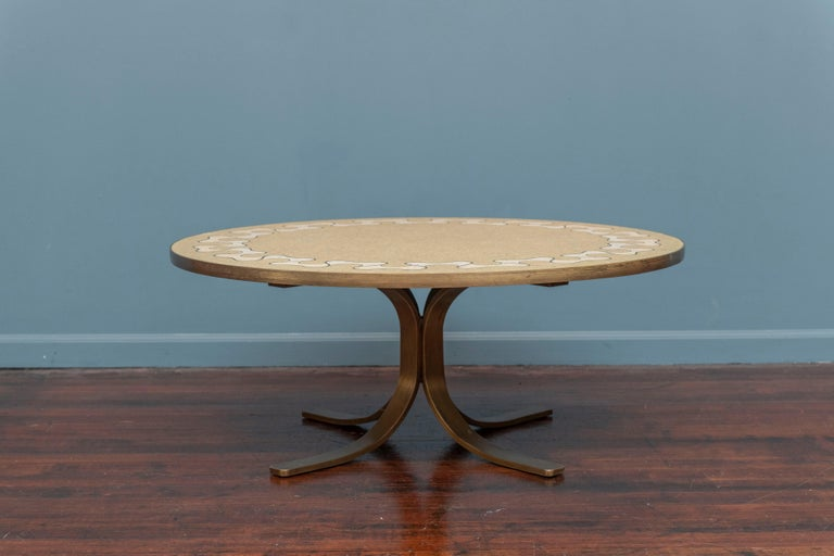 Mid-Century Italian terrazzo inlaid round coffee table with a patinated brass four leg base. The inlaid top is a ribbon fold pattern with brass trim. High quality construction and attention to detail, ready to install.