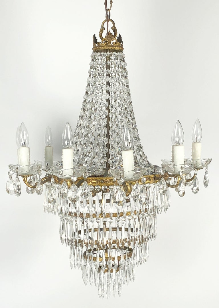 A beautiful Italian thirteen-light hanging fixture or chandelier of gilt metal and crystals, in the Empire style, featuring a crown over cascading pendants, with a ring of ten lights around the circumference surrounding a three light center, and