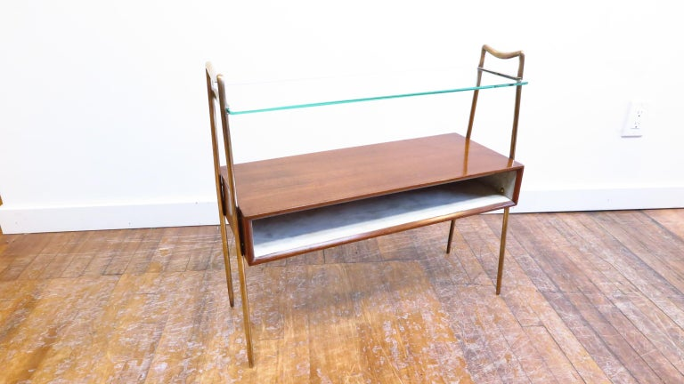 Midcentury Italian tiered side table. Italian tiered side table with parchment lined interior. Makore wood box having a parchment lined compartment supported by brass sculpted handle arches with a upper glass shelf. Beautifully designed table having