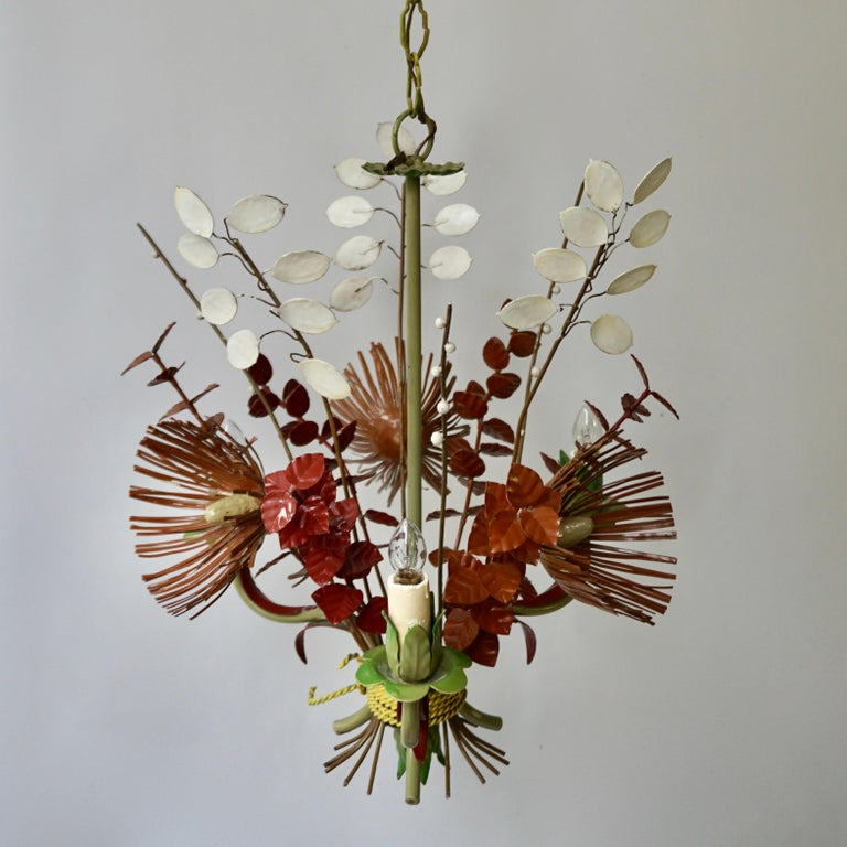 A wonderfully hand painted tole three-arm light fixture with flowers and scrolling leaves.   Measures: Diameter 45 cm. Height fixture 45 cm. Total height including the chain and canopy 100 cm.  Needs to be rewired.