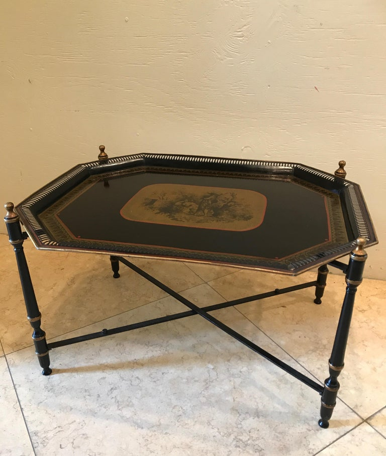 Black and gold tole tray table with a central scene.