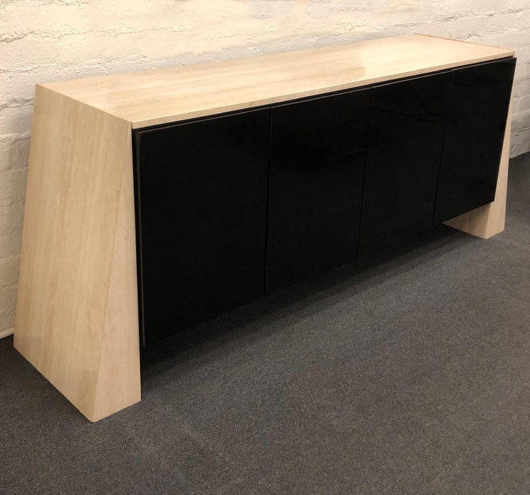 A spectacular polish Italian travertine and polish black lacquer credenza from the 1980s. The inside is all black on one side there's a drawer with a dinner wear organizer and an adjustable shelf. Newly professionally polished.