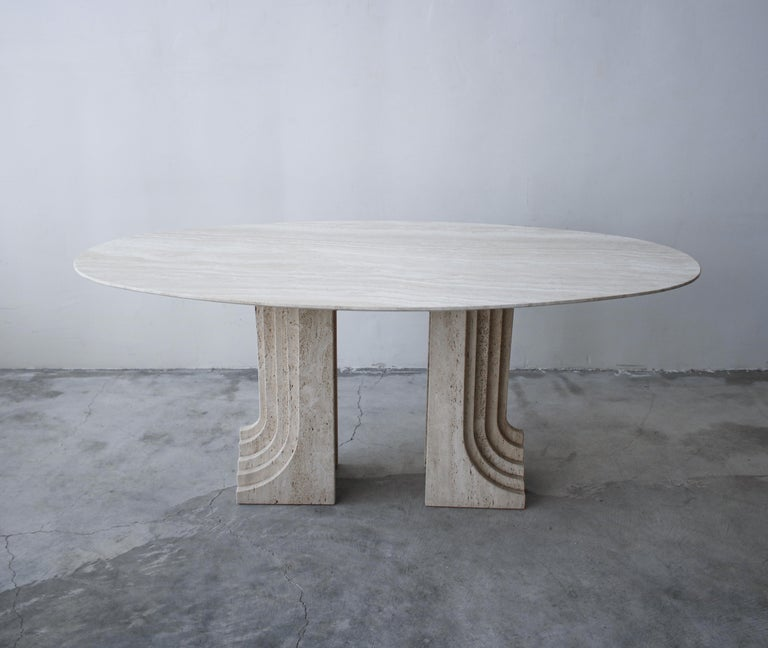 Nothing short of amazing. A gorgeous solid travertine dining table by Carlo Scarpa. A gorgeous polished travertine top is supported by a pair of honed travertine pedestals designed in a staggered, architectural pattern giving them extreme depth and