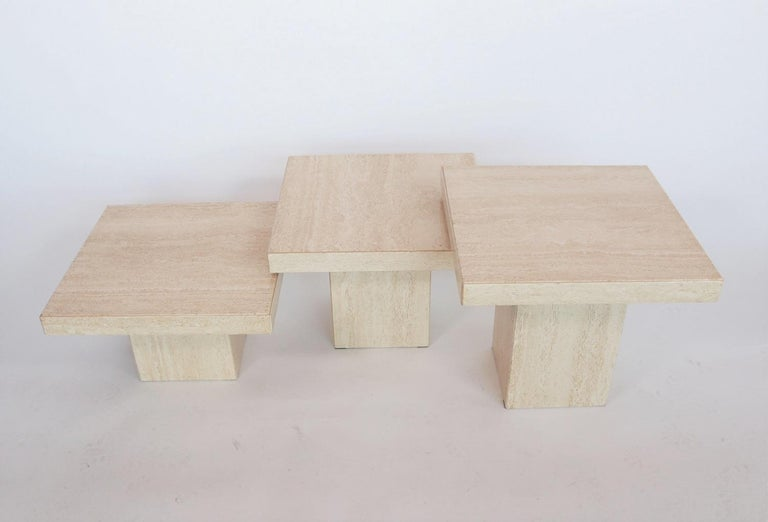Gorgeous set of three different travertine marble coffee tables from the rich Italian Regency period during the 1970s. Made in Italy. The tables have a beautiful cream color and gorgeous marble structure. The three square bases are of different