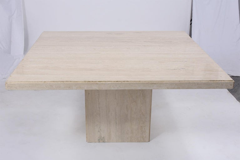 A fabulous stone dining table crafted out of travertine marble. This table has an eye-catching has a large square top with rounded edges and seats on a floating base, This Minimalist dining marble table would make a great addition to any home or