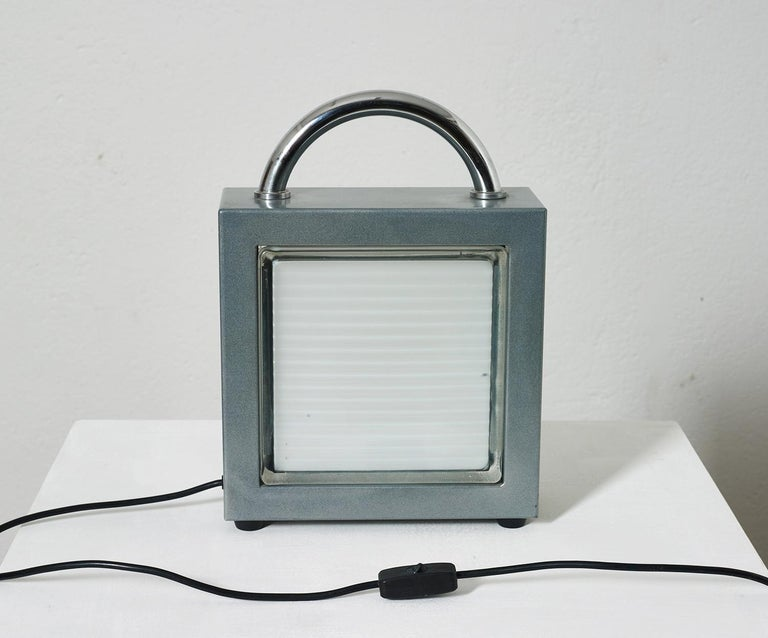 Italian Valigetta table light by Matteo Thun for Bieffeplast 1988, Memphis style  This table light is inspired by the glass blocks used in construction also called vetrocemento. Here the glass block serves as diffuser which is housed in sturdy