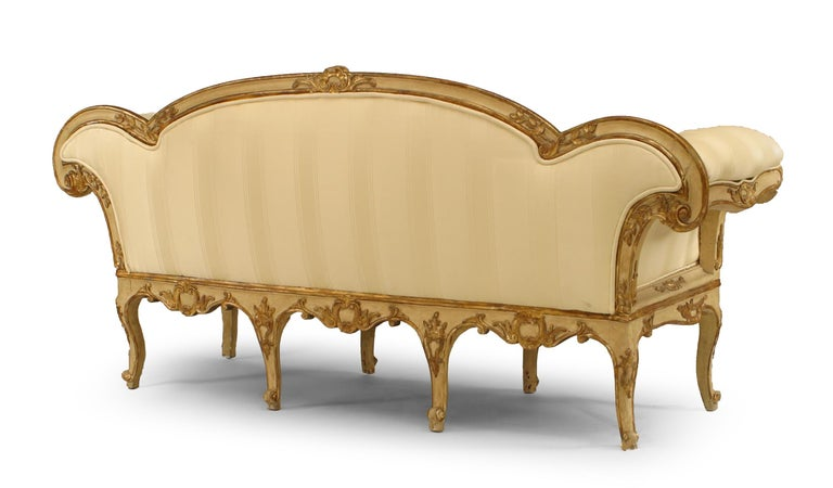 Italian Venetian (18th century) cream painted and gilt trimmed carved floral design settee with roll arms and carving on back (restorations to interior frame).