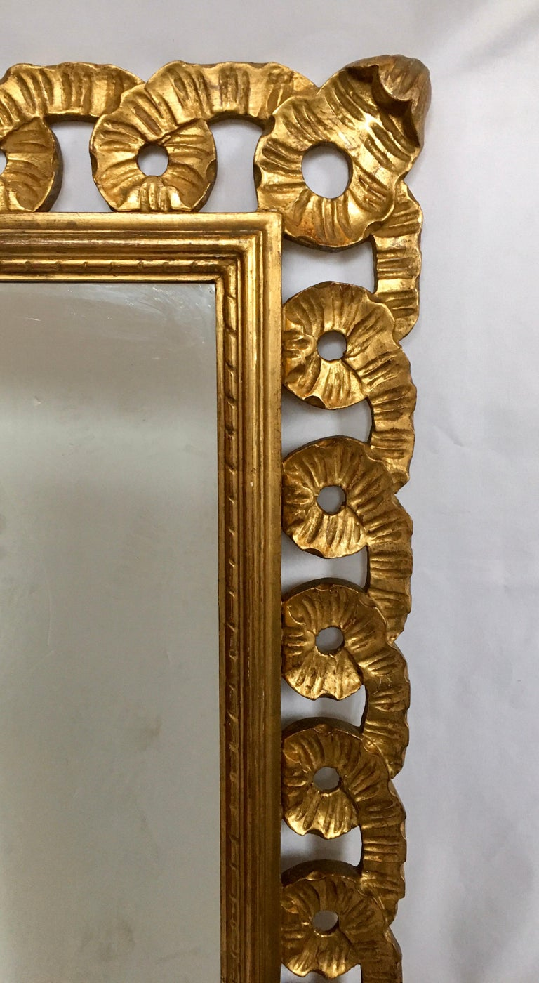 Beautifully detailed Italian Venetian wall mirror featuring a hand carved fluted and scalloped ribbon design. This large sculptural rectangular giltwood wall mirror can be mounted both vertically or horizontally.