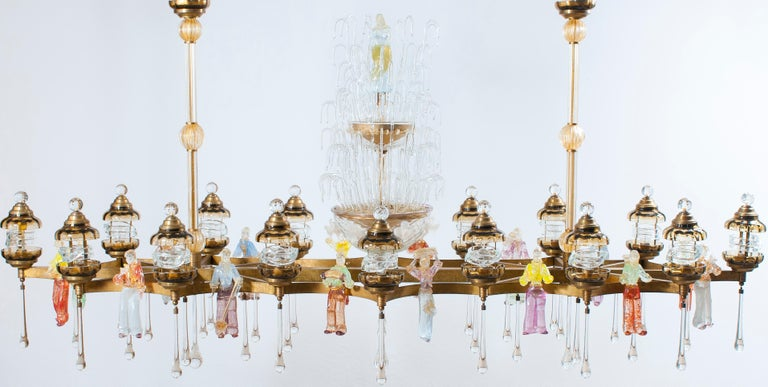Astonished, massive and elegant Italian Chandelier in Blown Murano Glass Colorful Statues and brass frame 1950s. The astonished portrait is composed by 17 statues of musicians and farmers, 18 lanterns surrounding the entire brass framework. The