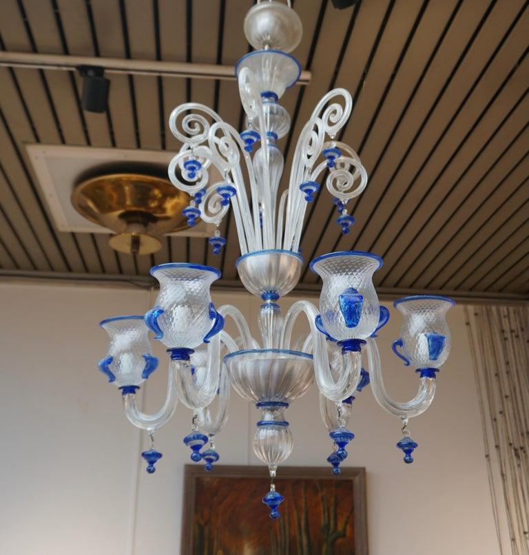Italian Venetian Murano (1970s) blue and transparent glass chandelier with 6 arms.  The light requires six single E14 screw fit lightbulbs (60Watt max.) LED compatible.  Measures: Diameter 27.5 inch - 70 cm. Height fixture 37.4 inch - 95