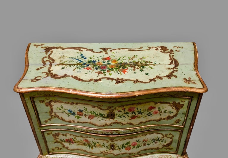 A very pretty Italian Rococo style serpentine 2-drawer commode, the green ground painted overall with foliate and gilt decoration within cartouches, resting on cabriole legs ending in stylized ball and claw feet.