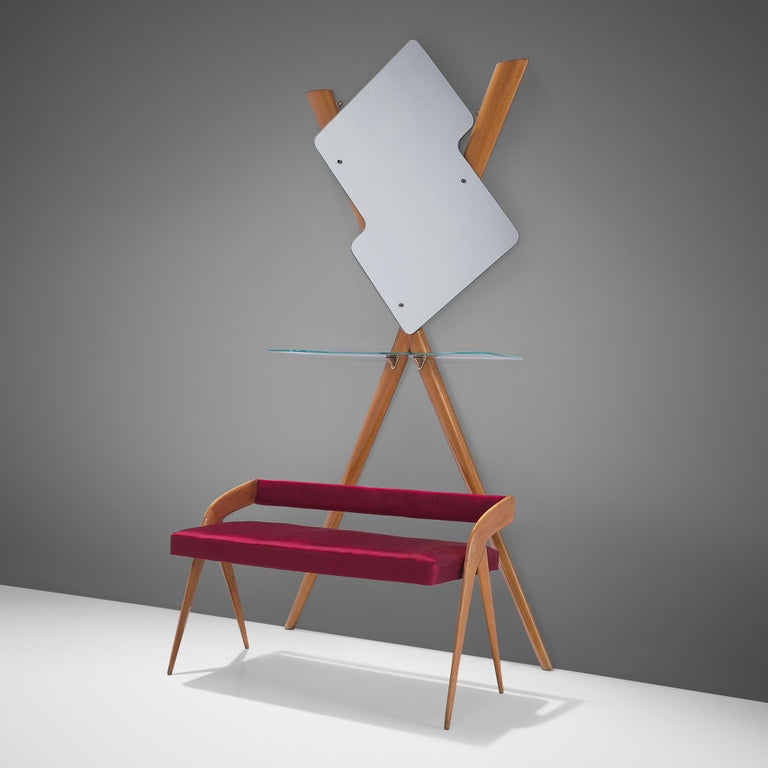 Vestibule set with settee and mirror, wood, red fabric, glass, Italy, 1950s  This elegant set is an ensemble of a small settee or bench together with a glass shelve and a free formed mirror. The set is executed in wood and features a playful,