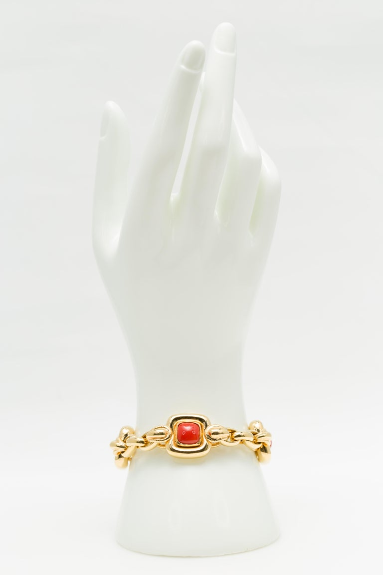 An Italian vintage cabochon Mediterranean Coral bracelet in 18K yellow gold, circa 1970. Featuring natural untreated cabochon Mediterranean Corals of a deep salmony red hue very well matched in size and color and set in 18K yellow gold, this stylish