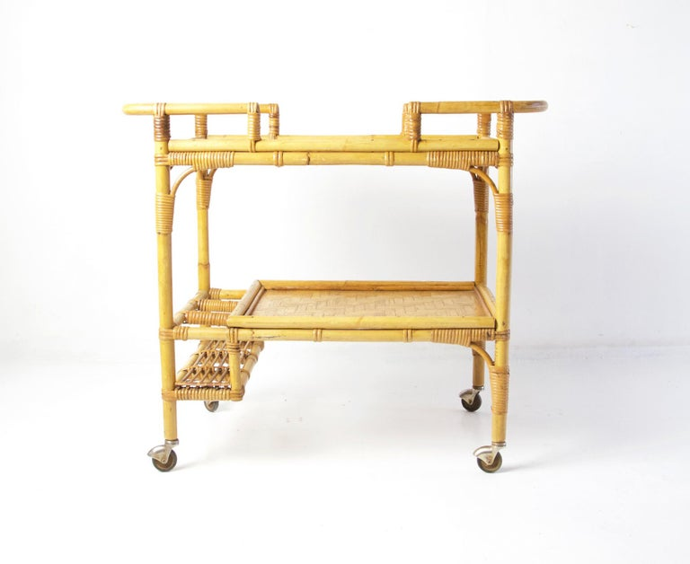 A vintage bar cart in bamboo, rattan and banana leaf with two tiers and space to hold three bottles. Has the original castors and is in overall great condition.