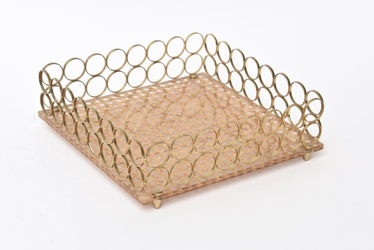 This lovely vintage Italian square tray has 2 rows of circles of brass as the borders and a caned base with a Lucite top. It is from the 1970s. It has 4 peg feet. Great for serving, for barware or for decoration. Tres chic! This in the style of