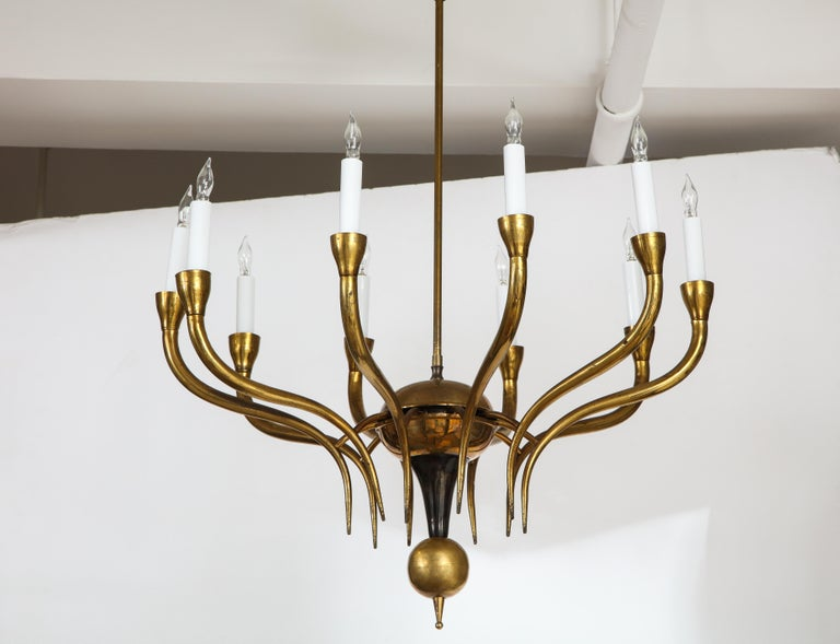 A simple and sophisticated Italian vintage brass chandelier consisting of ten elegantly outstretched arms extending from a circular central support, with a brass ball finial at its base, underneath a painted black metal geometric shape connecting