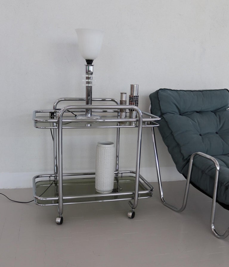 Elegant service trolley or bar cart with chromed metal frame and 4 rollers.
