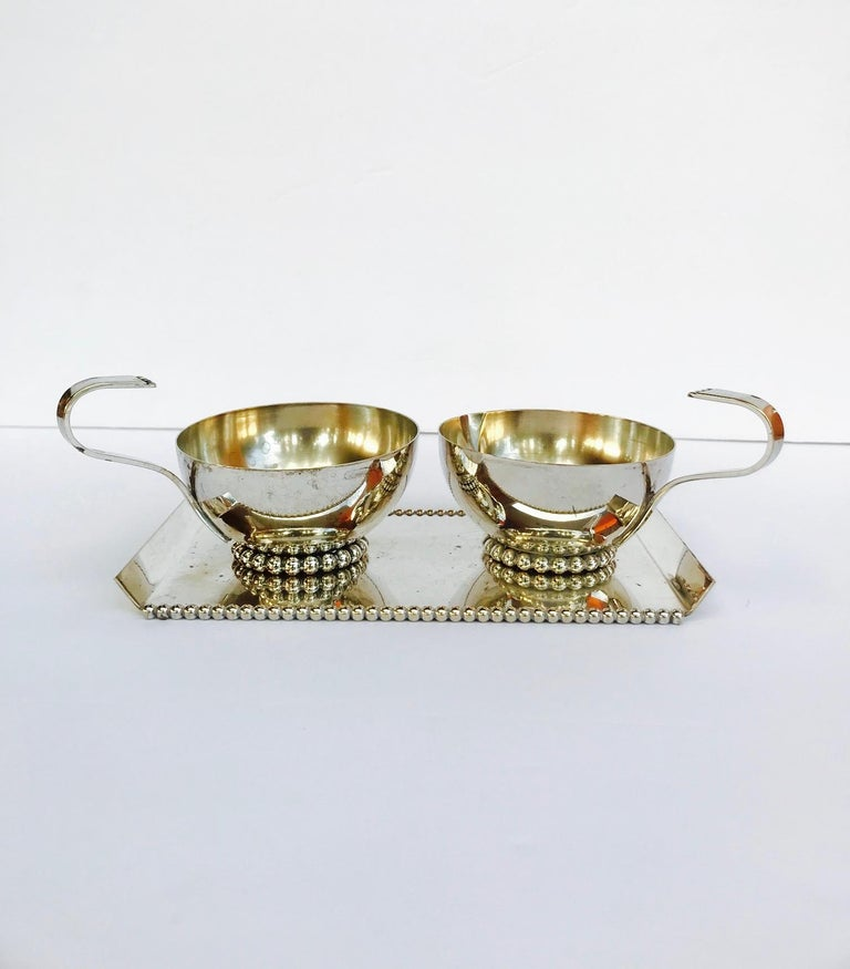 Exquisite vintage serving set handcrafted from silver plated metal. The set features handled creamer with spout and handled sugar bowl. Both pieces have elegant saucer forms with stylized hand forged handles. The set includes a modernist serving