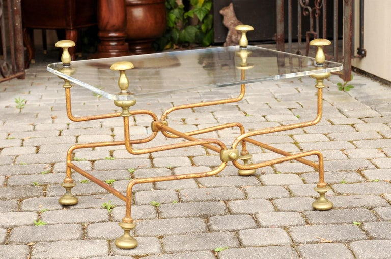 An Italian vintage brass cocktail table from the mid-20th century, with Lucite top. Born in Italy during the midcentury period, this cocktail table features a rectangular Lucite top, accented with eye-catching finials in its corners. The table is