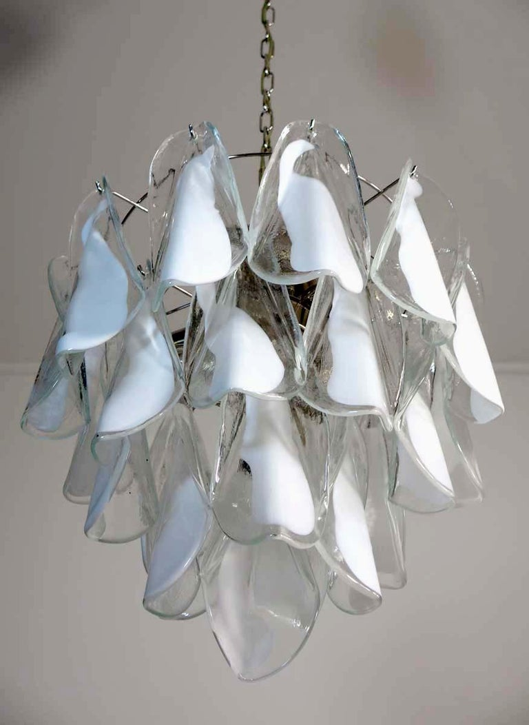 """Rare Italian vintage Murano chandelier. The fixture is made up of 24 individual hand blown glass elements hanging (transparent and white """"lattimo"""") from a chrome frame. Each piece clear with white centre. Period: 1960s-1970s Dimensions: 46.45"""