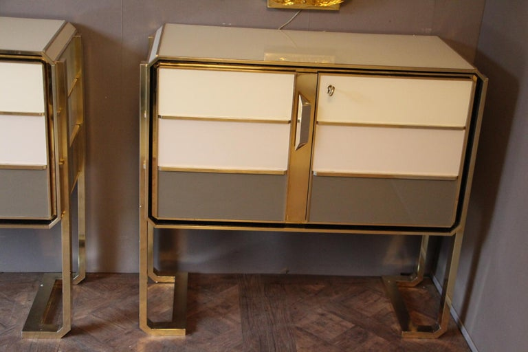 Superb pair of Italian fine design one of a kind cabinets in golden polished brass, ivory white, beige and grey color Murano glass featuring 2 doors. The top is covered in beige color Murano glass. Solid wood structure. These cabinets have been