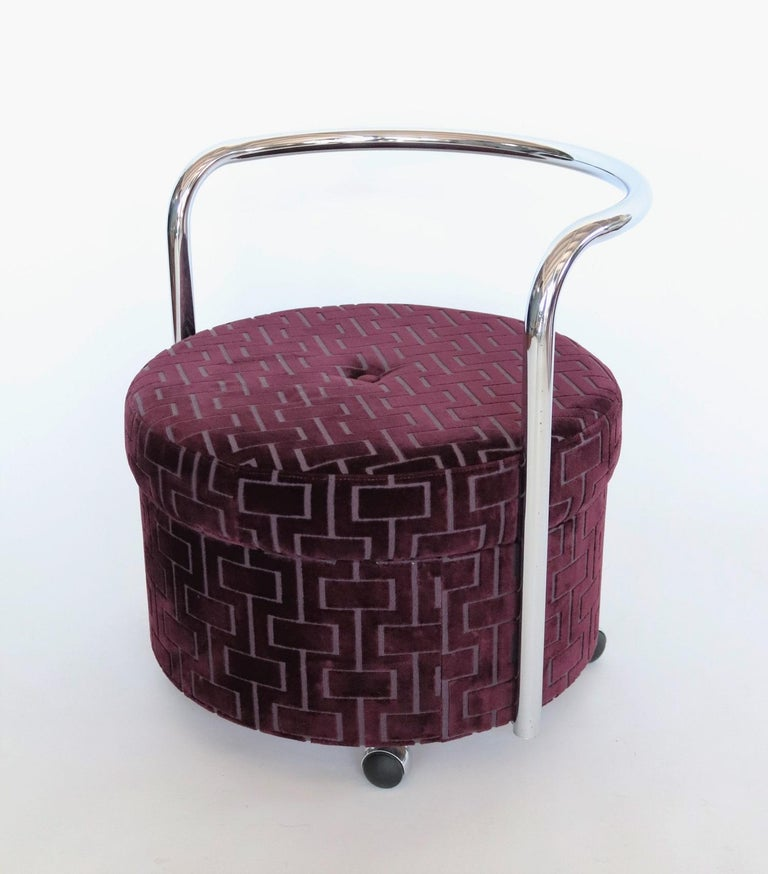 Beautiful rolling ottoman or pouf original from the 1970s with chromed curved backrest and four wheels. The pouf have been re-upholstered with quality velvet in purple. The wheels are rolling smoothly. Beautiful vintage object.