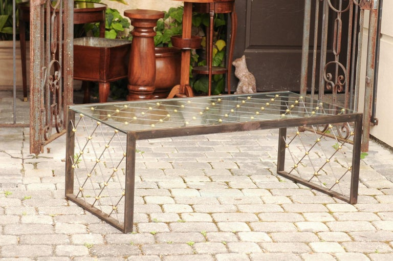 A French steel and brass cocktail table from the mid-20th century, with glass top and diamond patterns in the style of and attributed to Jean Royere. Born in France during the mid-century period, this stylish cocktail table features a rectangular