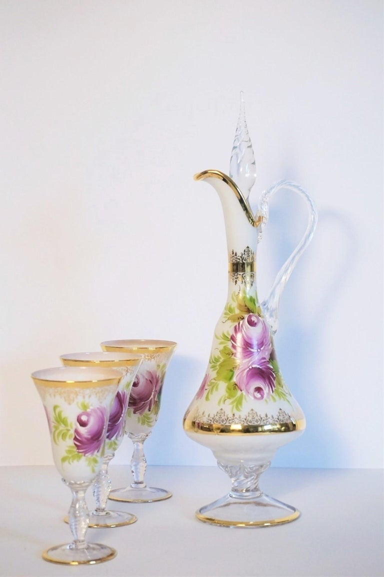 This lovely, elegant Italian water carafe and three glasses set is made of white opaline crystal glass, hand painted with delicate flowers, leaves and gilded decor, carafe with a wonderful tall lid. All pieces are signed by the artist.