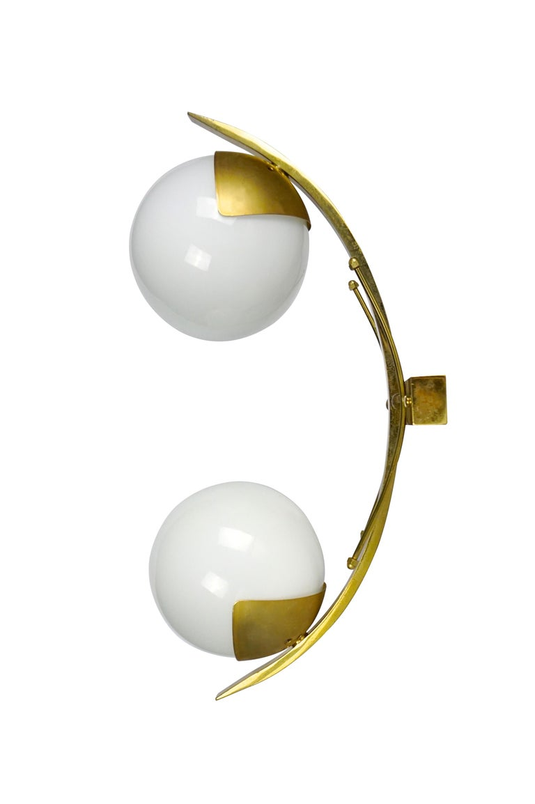 Elegant pair of wall lights or sconces each holding two opaline glass globe shades and brass frame, circa 1960's. -Made in Italy -Dimensions: H 42 x W 15 x D 23 cm.